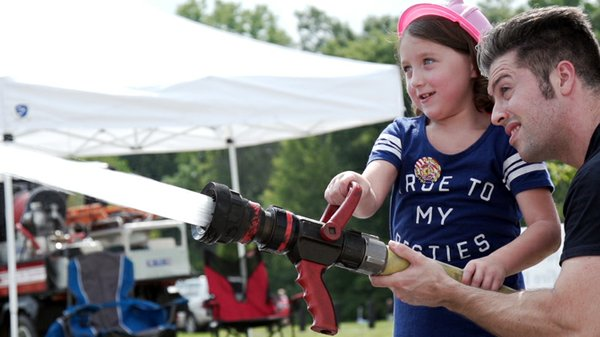 Girl with fire hose at EcoFest.jpg