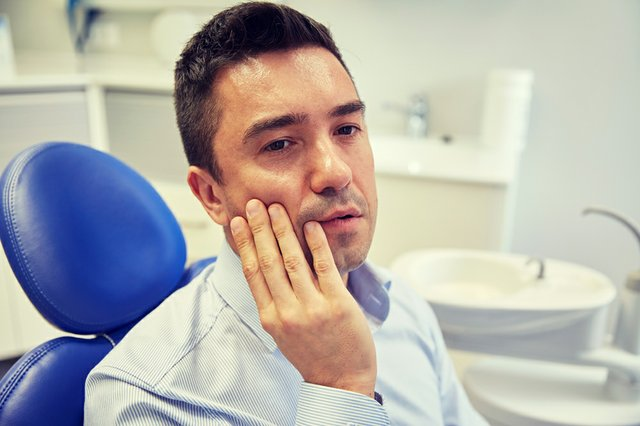 man having toothache and sitting on dental chair